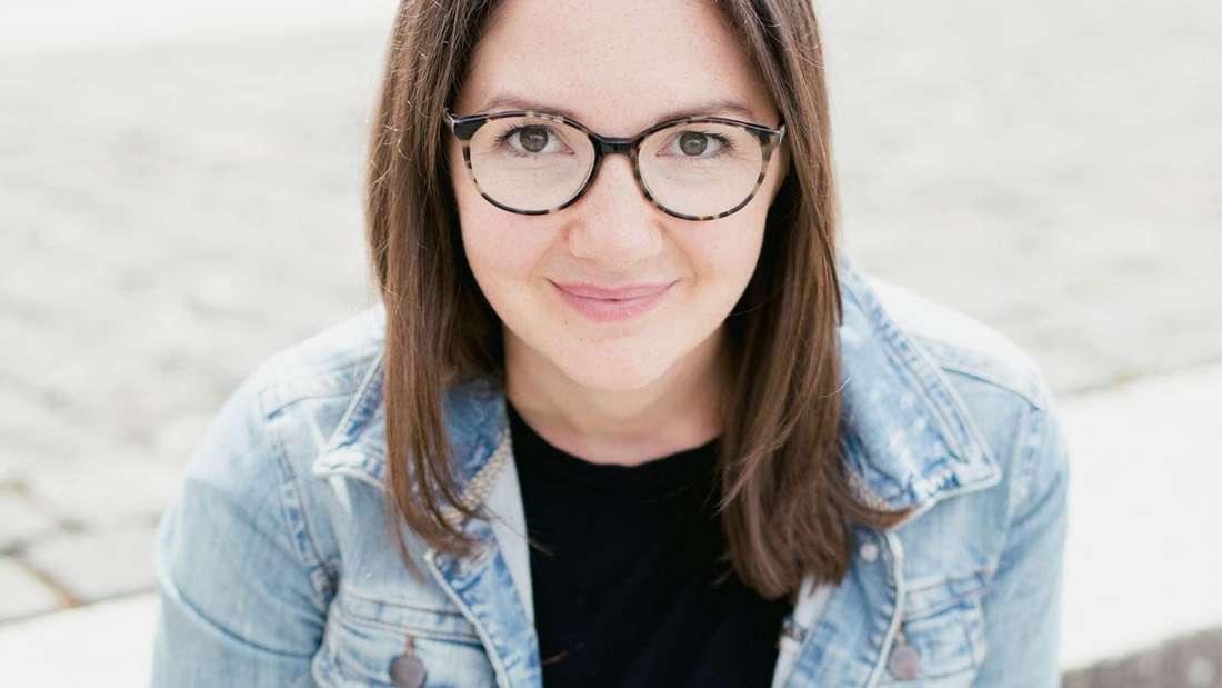 Julia Allmann aus Köln auf einer Steintreppe. Sie hat braunes Haar, trägt eine Brille und eine blaue Jeansjacke.