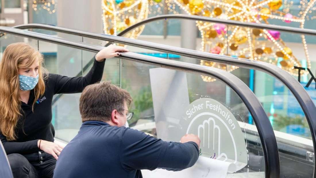 UVIS-Gründerin Tanja Zirnstein sieht zu, wie ein Techniker die UVC-Beschichtung auf einer Rolltreppen anbringt, die diese virenfrei machen soll.