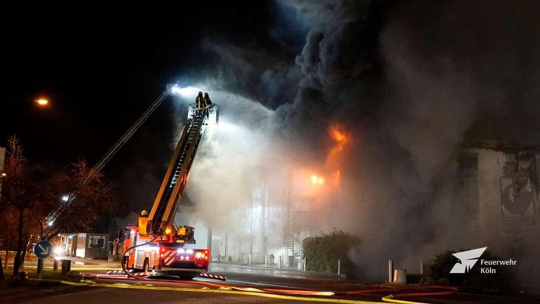 Mit einem Löschfahrzeug kämpfen Feuerwehrleute in Köln gegen die Flammen in einer Lagerhalle an.