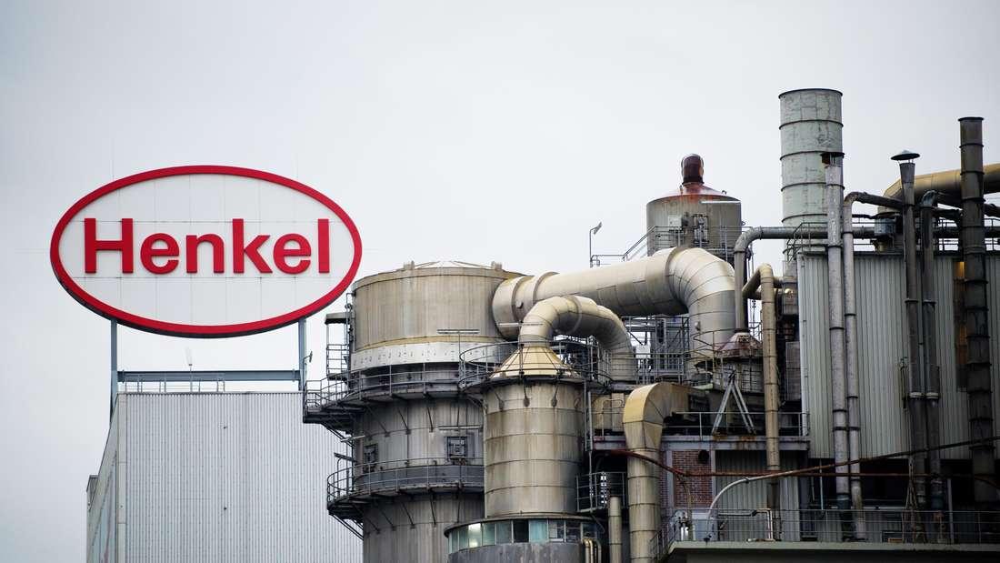 Ein Logo der Henkel AG auf einem Gebäudedach hinter einer Produktionsanlage auf dem Werksgelände in Düsseldorf