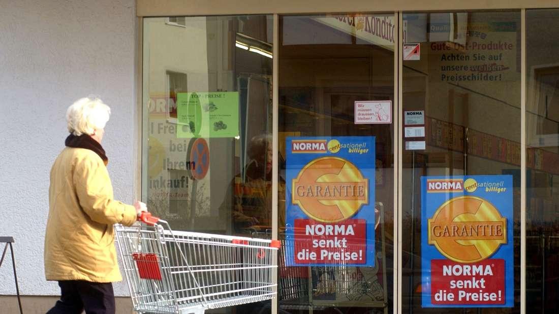 Eine Frau geht in einen Discounter einkaufen, der mit Billig-Angeboten lockt (Norma)
