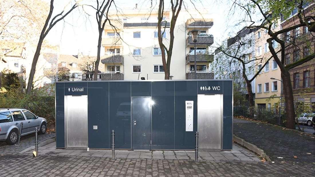 Ein Toilettenhäuschen auf einem Platz. Im Hintergrund Häuser, links ein Auto