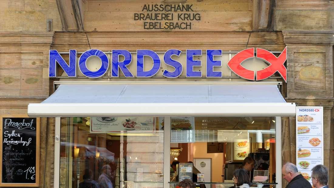 Kunden stehen Straßenverkauf einer Nordsee-Filiale an