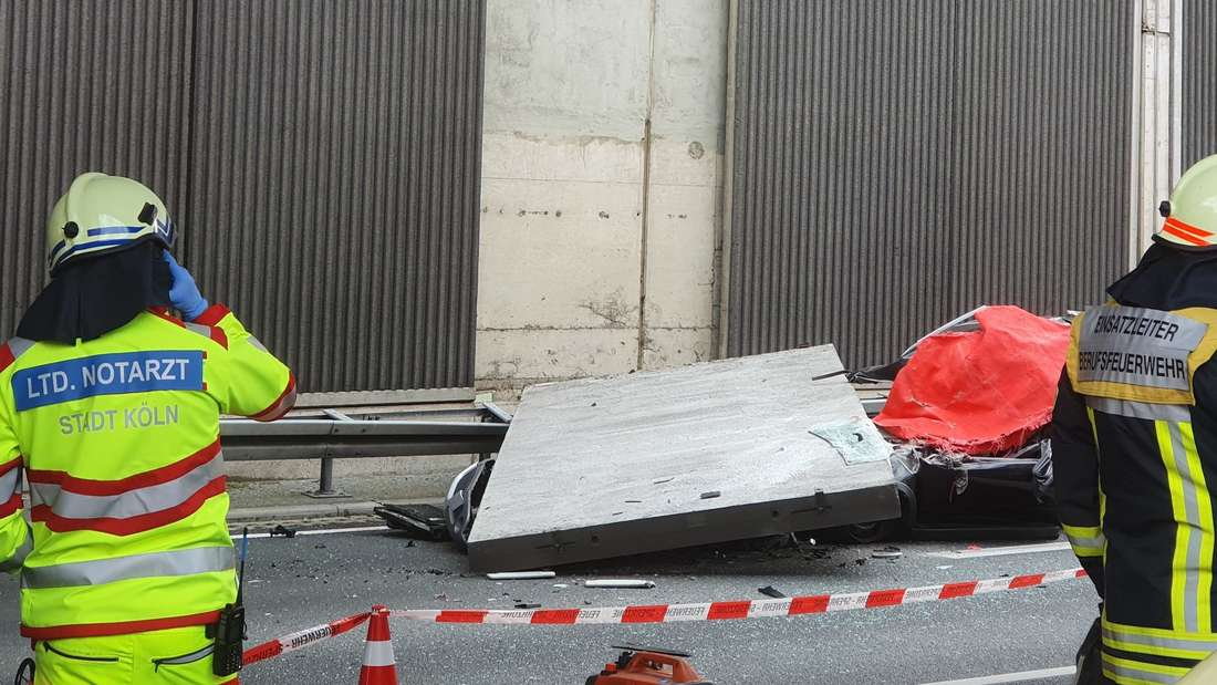 Einsatzkräfte sichern eine Unfallstelle. Im Hintergrund sieht man eine Betonwand, die ein Auto unter sich begraben hat.