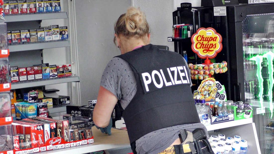 Polizistin (von hinten zu sehen) durchsucht Kiosk-Tresen