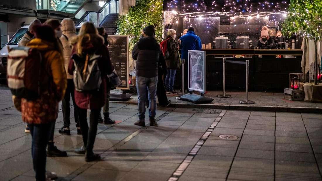 Menschen stehen an einem Glühweinstand in Stuttgart an, um sich ihr Heißgetränk to go abzuholen.