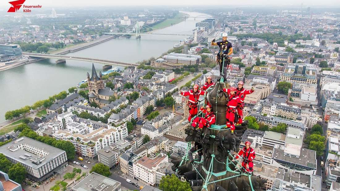 Feuerwehrleute stehen in Uniform auf dem Kölner Dom.