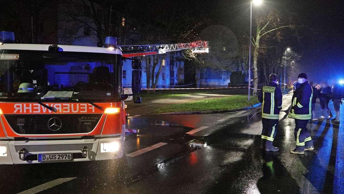 Polizei und Feuerwehr stehen neben einem Einsatzfahrzeug.