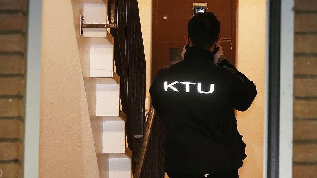 Ein Kriminal Techniker fotografiert im Treppenhaus eines Mehrfamilienhauses.