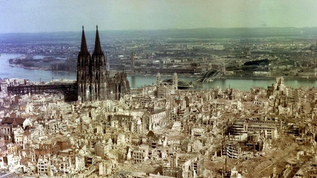 Köln 1945: Zerstörte Innenstadthäuser und Hohenzollernbrücke durch Bombenangriffe, nur der Dom ragt noch auf.