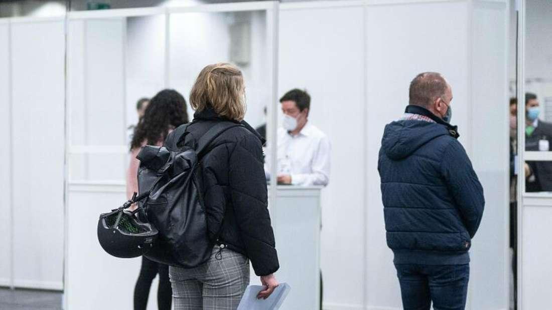 Darsteller stehen während eines Probedurchlaufs im Impfzentrum Köln an Registrierungsschaltern an.
