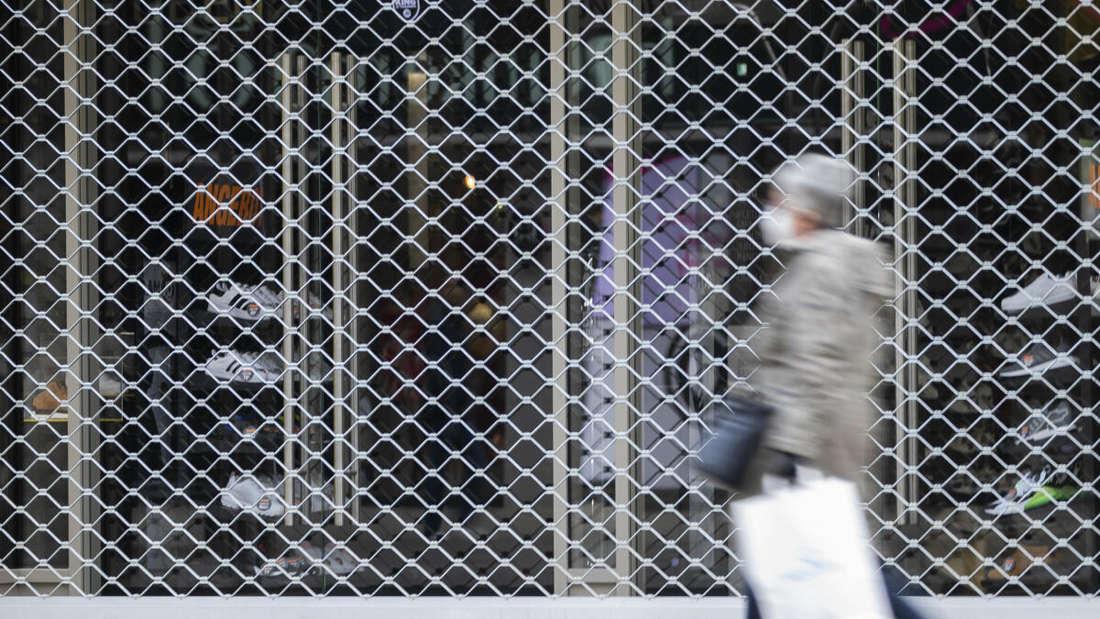 Eine Frau mit einer Einkaufstasche geht an einem geschlossenen Laden in der Königsstraße vorbei.