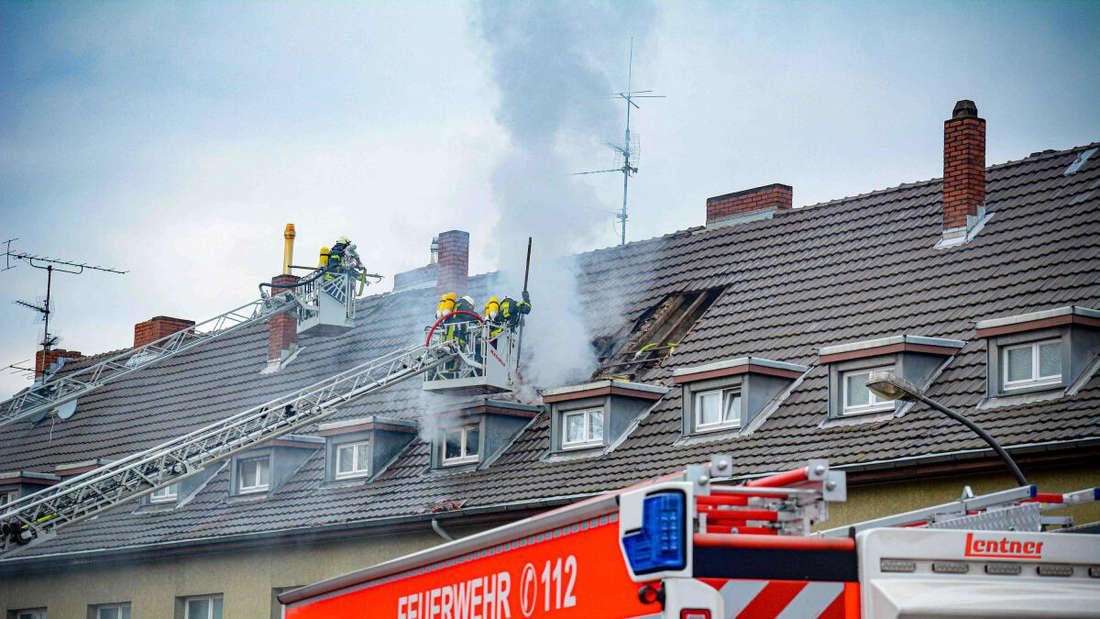 Einsatzkräfte der Feuerwehr löschen einen Brand im Dachgeschoss.