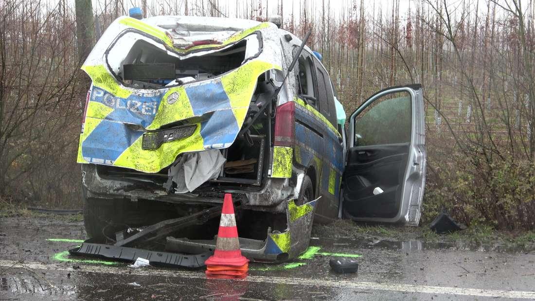 Ein beschädigtes Polizeiauto steht neben einer Landstraße in der Böschung.