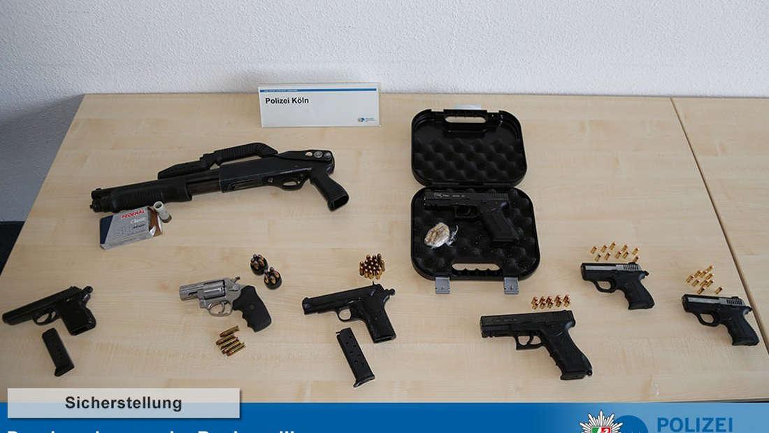 Waffen und Munition liegt aufgereiht auf einem Tisch.
