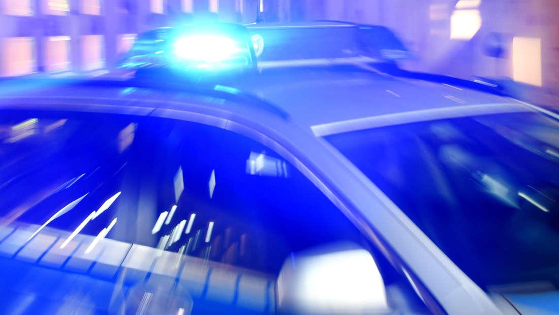 Ein Streifenwagen der Polizei steht mit eingeschaltetem Blaulicht auf der Strasse.