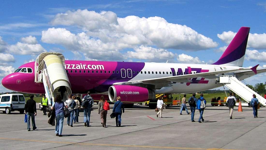 Passagiere laufen zu einem Airbus von Wizz Air, die auf dem Rollfeld des Danziger Flughafens steh