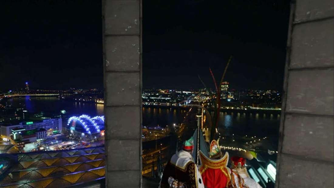 Das Kölner Dreigestirn blickt vom Kölner Dom aus über die Stadt. (Screenshot)