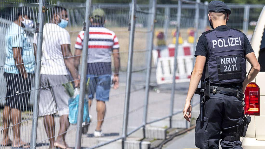 Ein Polizist nähert sich einer Gruppe Menschen, die hinter einem Bauzaun entlang gehen. Alle tragen einen Mund-Nase-Schutz.