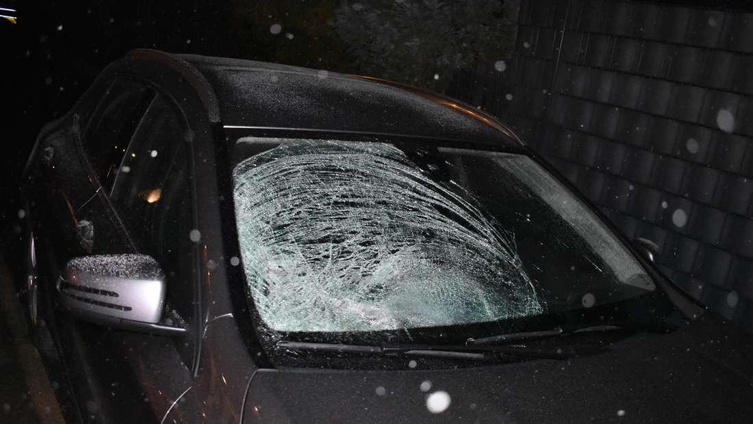 Die geborstene Windschutzscheibe eines schwarzen Fahrzeuges
