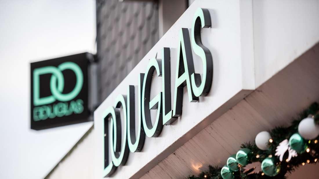 Der Schriftzug und das Logo von Douglas hängen an einer Filiale.