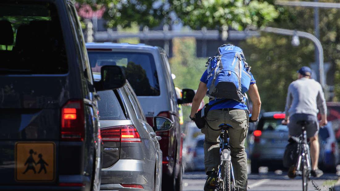 Eine vielbefahrene Straße mit zwei Fahrradfahrern auf ungesicherten Radwegen
