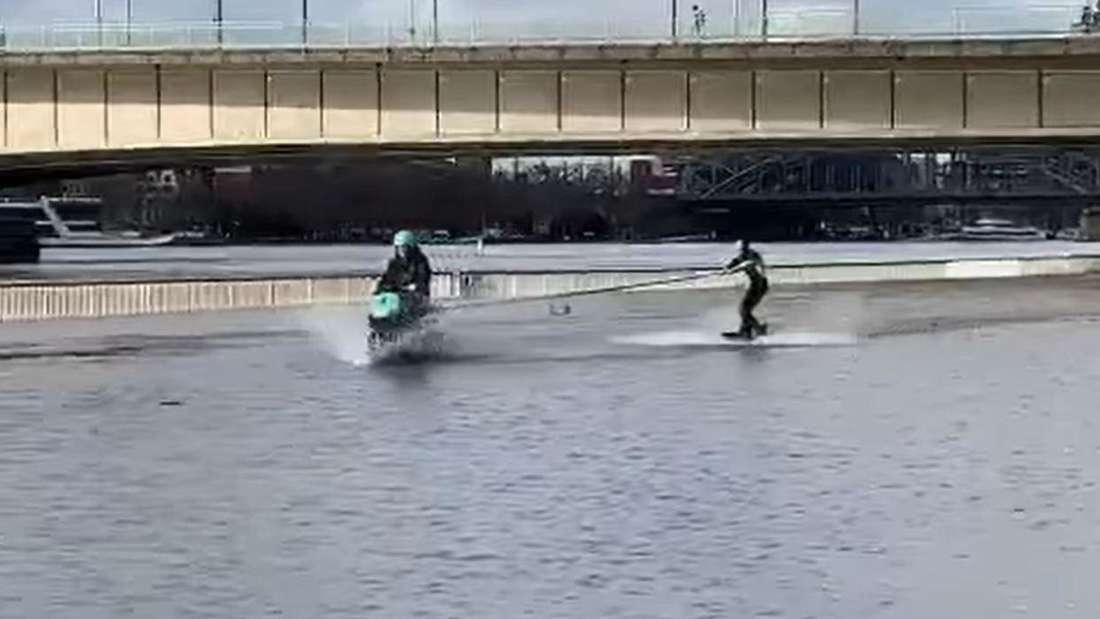 Ein Motorroller fährt durchs Hochwasser auf der Rheinpromenade in Köln und zieht einen Wakeboarder hinter sich her.