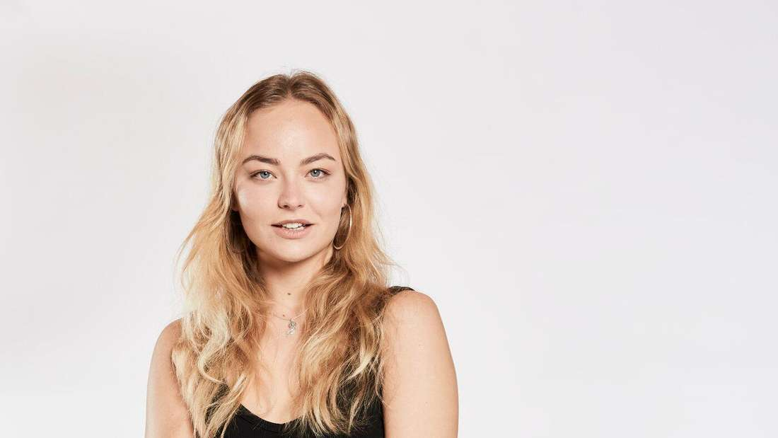 Topmodel-Kanidatin Elisa aus Dortmund posiert vor der Kamera und greift mit ihrer rechten Hand über ihren Bauch zum linken Ellenbogen.