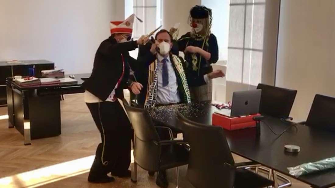 Zwei verkleidete Mitarbeiterinnen stürmen eine Live-Schalte des Düsseldorfer Oberbürgermeisters Stephan Keller