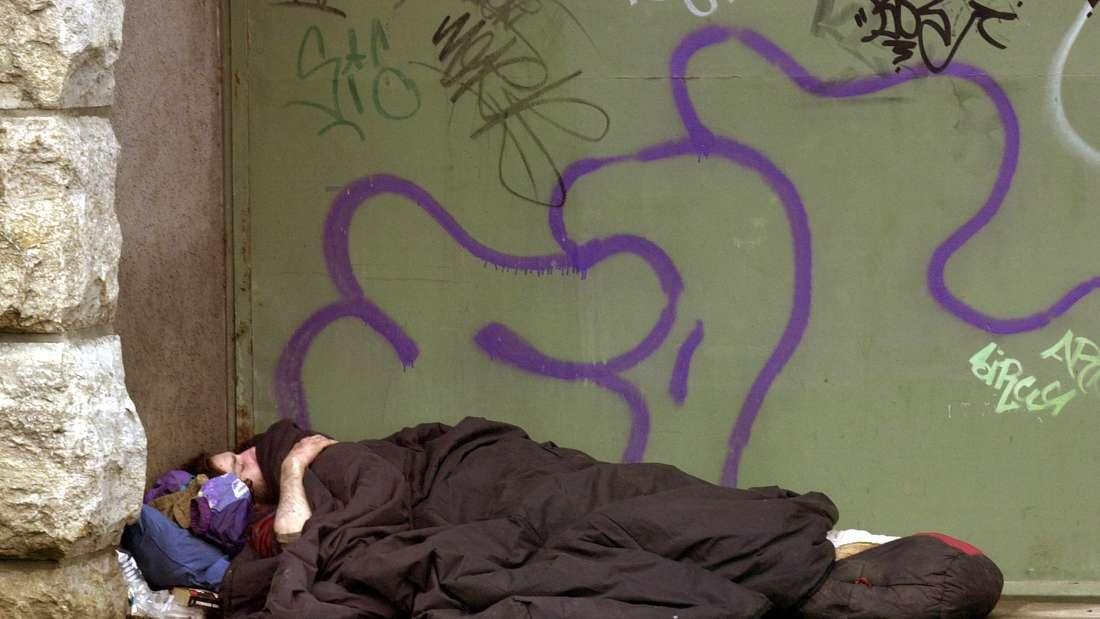 Ein Obdachloser schläft unter der Brückenzufahrt der Hohenzollern-Brücke in Köln