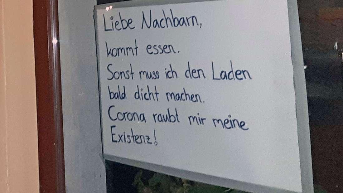 Im Fenster eines Imbiss in Köln hängt ein Zettel, der die Nachbarn bittet, die Wirtin zu unterstützen.