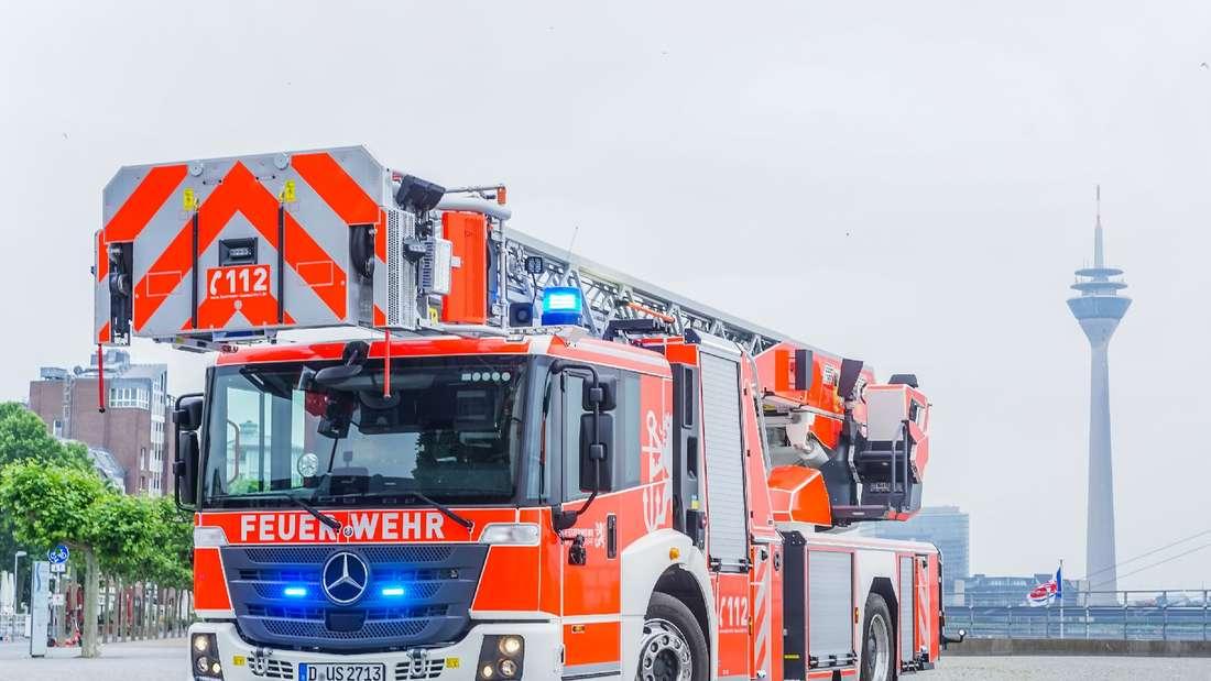 Fahrzeug der Feuerwehr Düsseldorf mit Drehleiter steht auf der Straße
