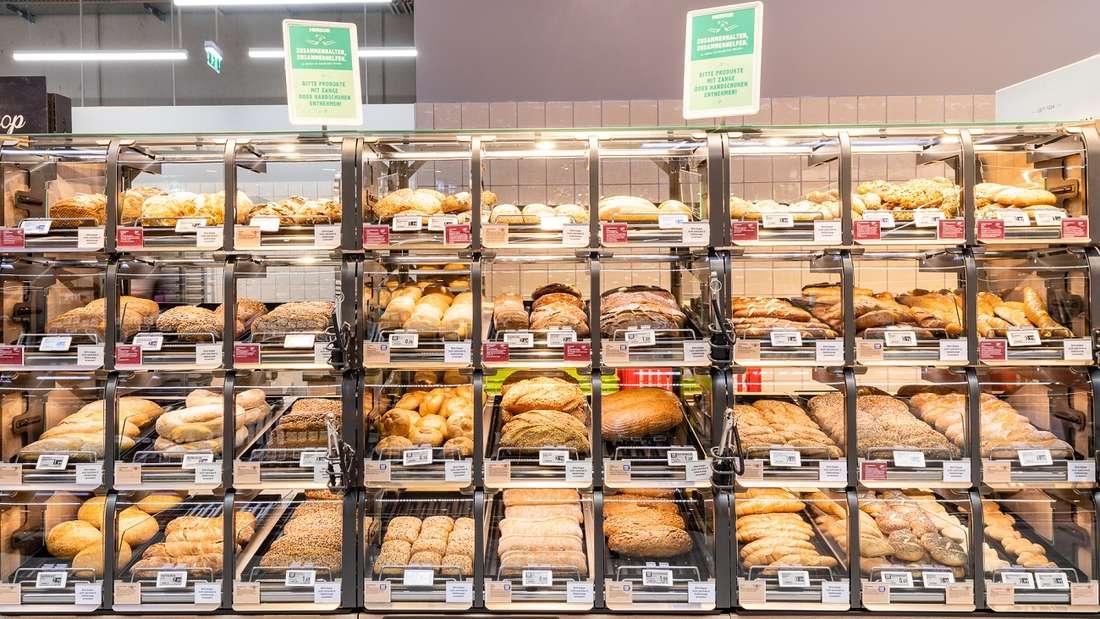Ein Backwarenregal, welches mit Brot und Brötchen gefüllt ist, im Supermarkt.