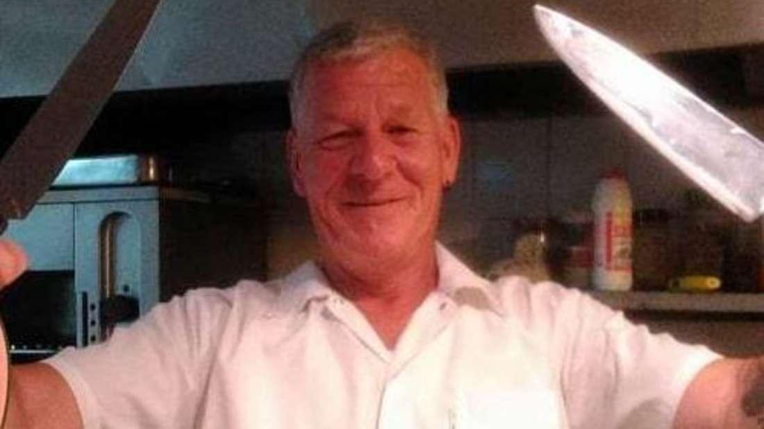 Gastronom Rudi Bluhm hält in einer Küche zwei Messer in der Hand.