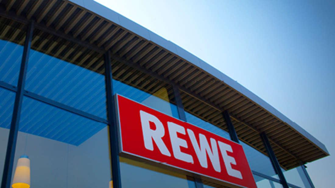 Rewe-Schild am Eingang eines Supermarktes.