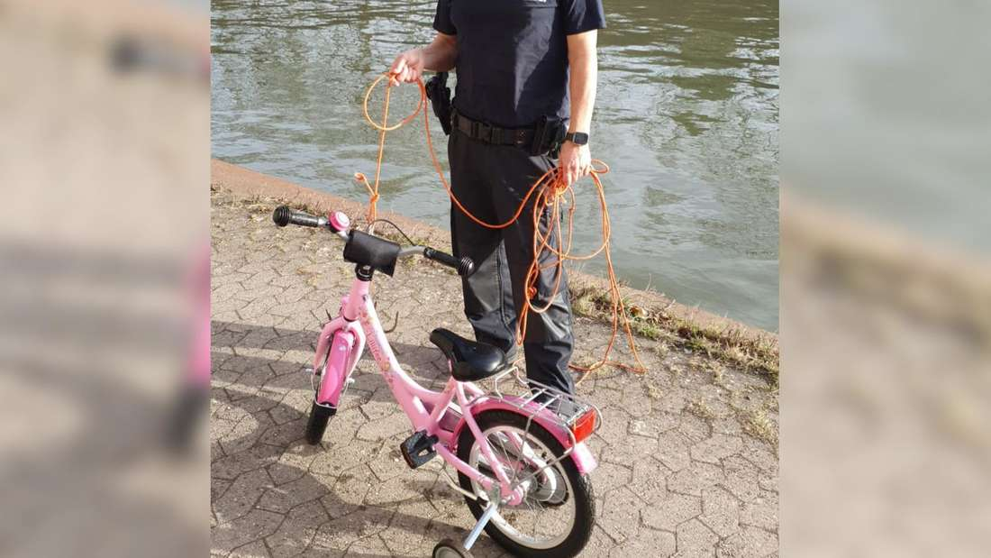 Ein Polizist steht am Mittellandkanal in Minden neben einem Kinderrad. Es war einer Vierjährigen ins Wasser gefallen.