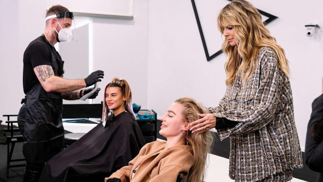 Die GNTM-Kandidatinnen Romina (l.) und Mareike (r.) sitzen auf dem Firseurstuhl. Heidi Klum schaut sich Mareikes Haare an.
