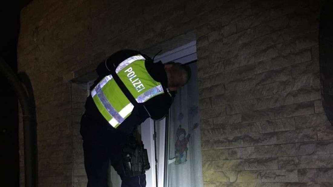 Polizist hantiert an einem Fenster