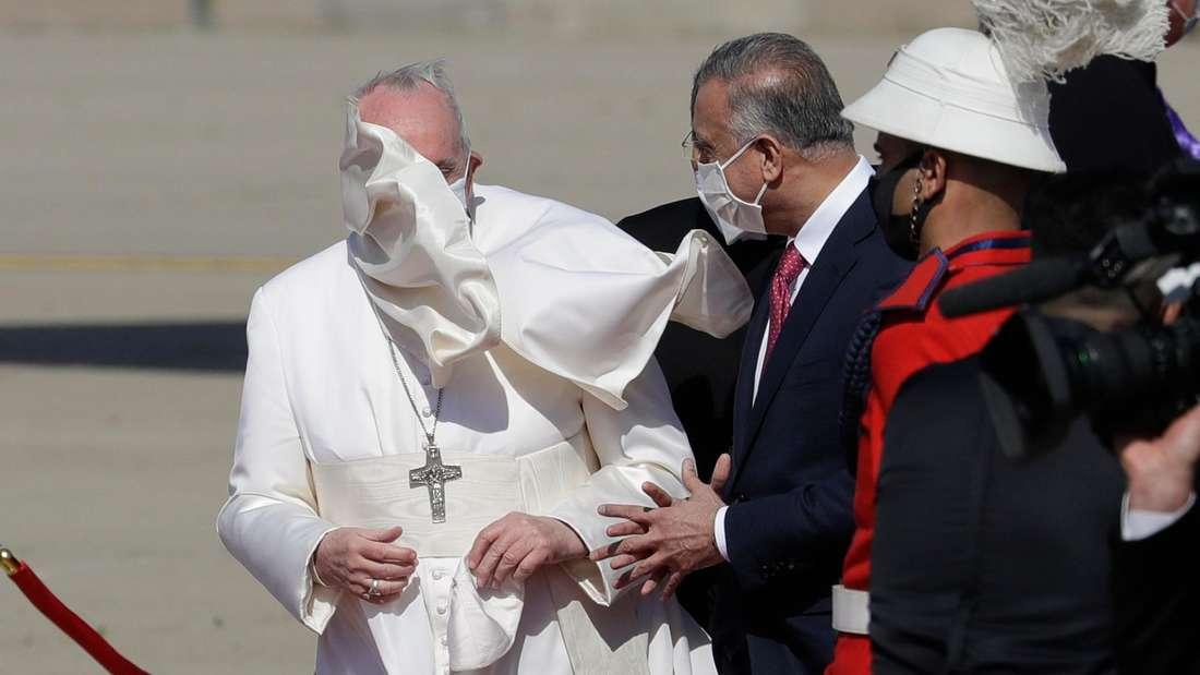 Papst zu Besuch im Irak: Ein Windstoß bläst den Mantel von Papst Franziskus beim Empfang am Flughafen in Bagdad hoch.