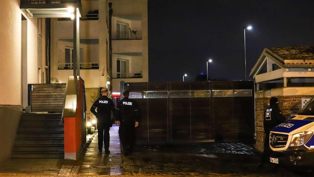 Polizisten stehen während einer Razzia wegen des Besitzes und der Verbreitung von Kinderpornographie an einem Wohnhaus.