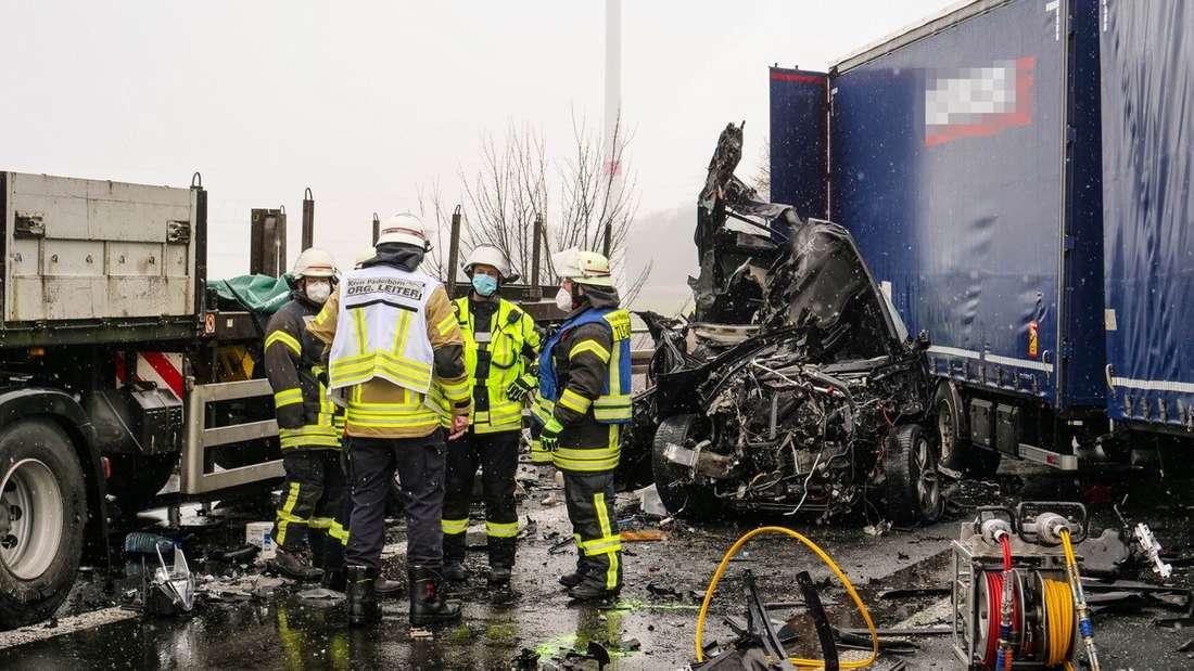Rettungskräfte stehen am Wrack eines Pkw, der unter einen Lkw auf der Autobahn 44 bei Lichtenau geraten war