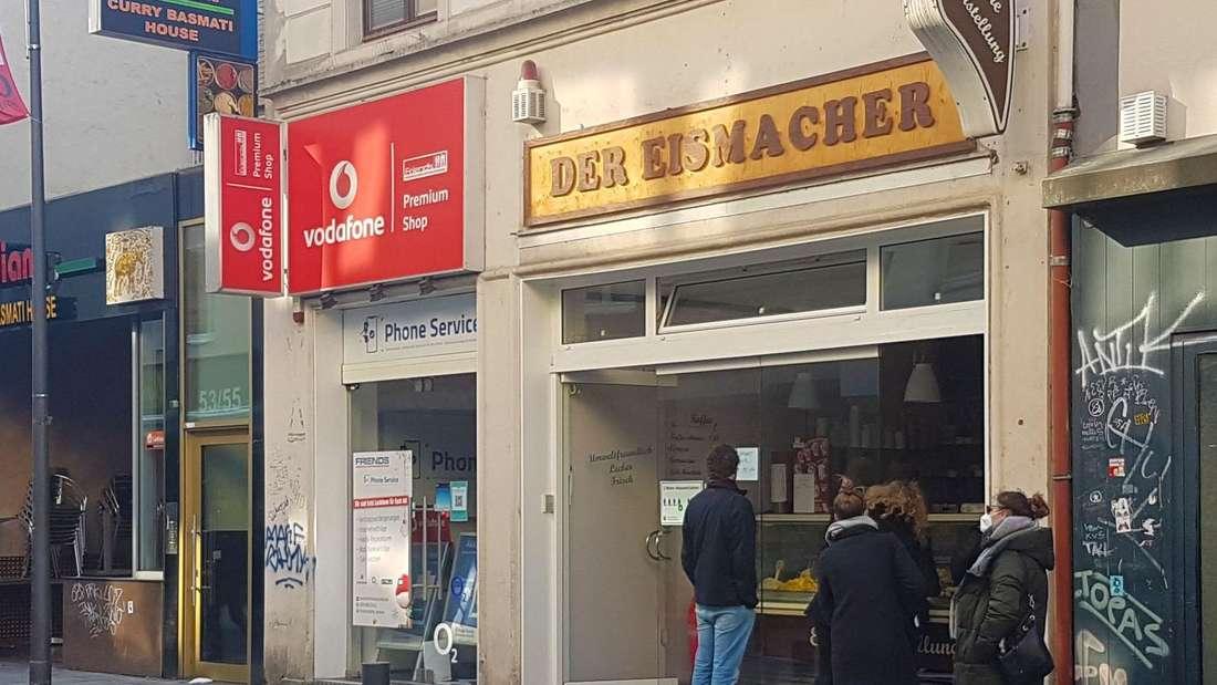 Eisdiele Eismacher in Köln Severinstraße. Leute stehen mit Masken davor.