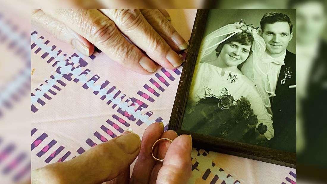 Hand der Seniorin mit Kopie ihres Eherings und Hochzeitsfoto