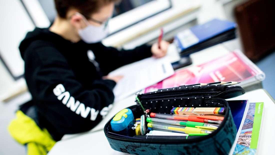 Ein Schüler der Oberstufe sitzt mit Mund-Nasen-Bedeckung in einem Klassenraum.