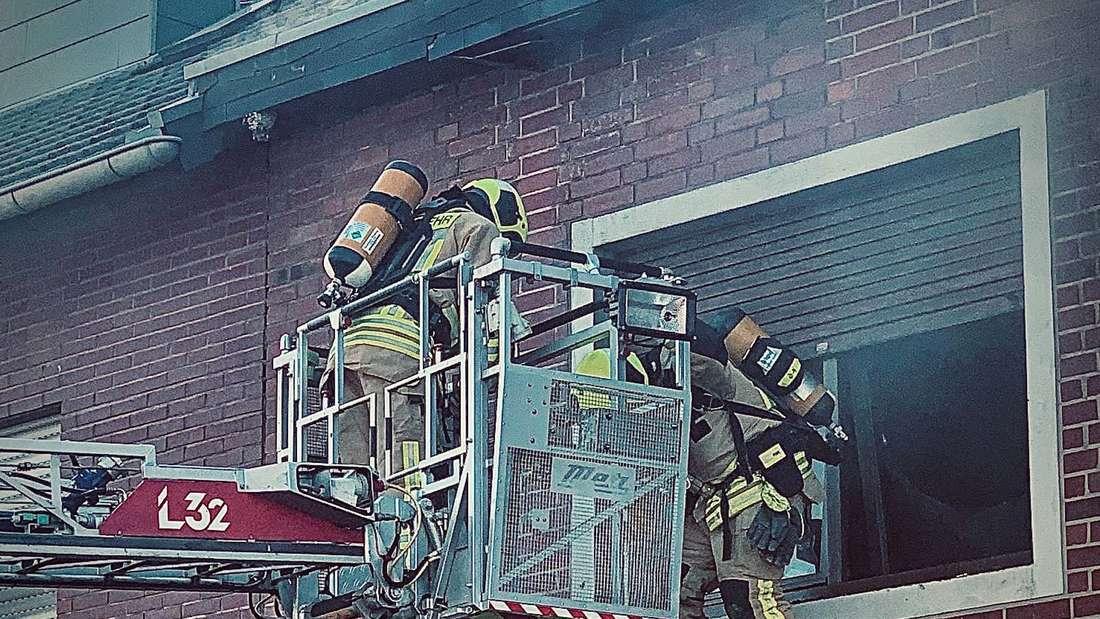 Feuerwehrmänner mit Atemschutz und Drehleiter im LÖscheinsatz