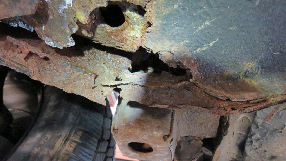 Durchgerostetes Metall unter einem Fahrzeug