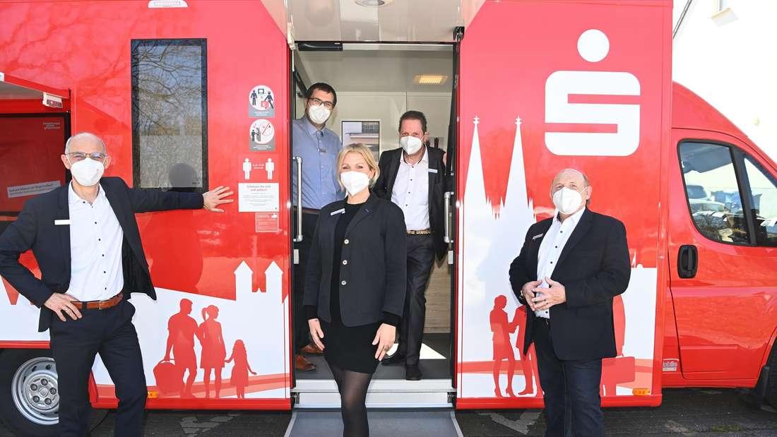 """Der Bus der Sparkasse Köln Bonn – davor stehen Volker Schramm und das Bus-Team der """"Mobilen Filiale"""""""