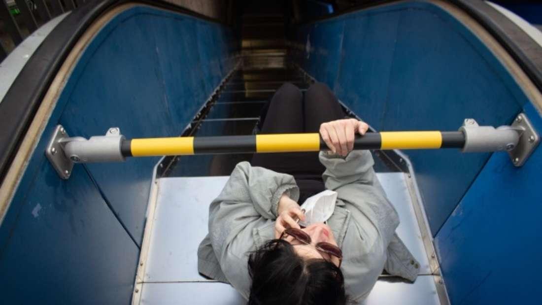 Eine Frau rutsch auf einer zu Rutsche umfunktionierten defekten Rolltreppe am Ebertplatz in Köln.