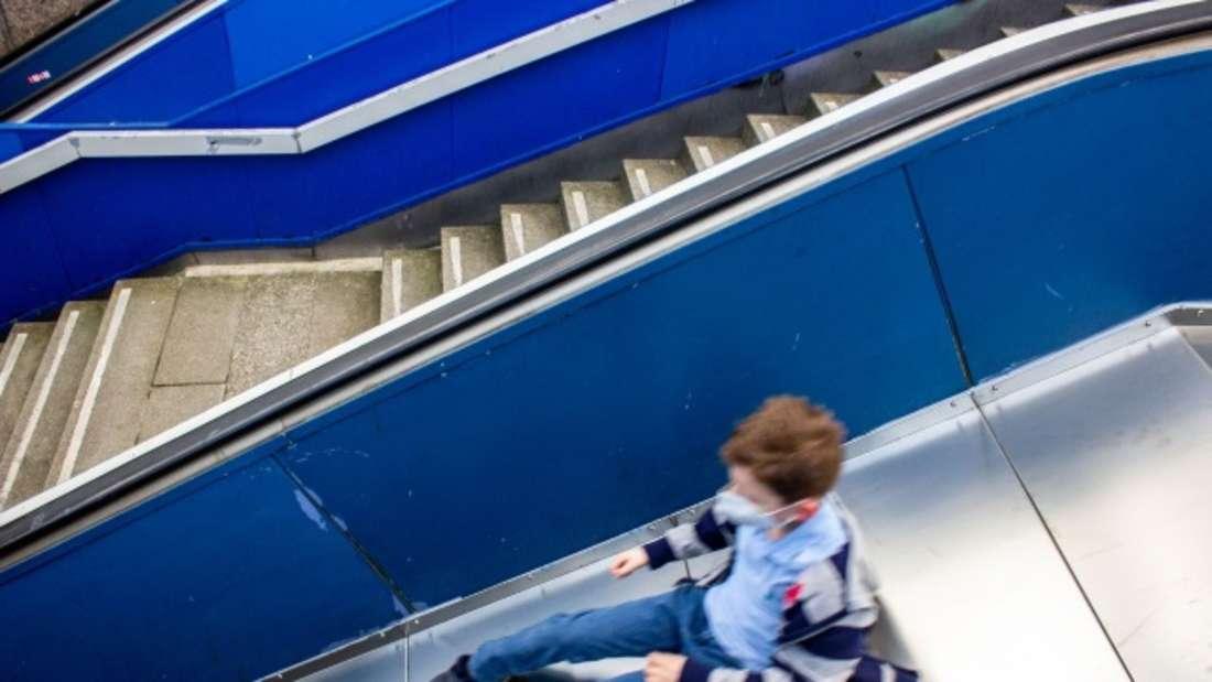 Ein Junge rutscht mit Maske auf einer Rutsche, die zuvor eine defekte Rolltreppe war, ins Untergeschoss des Ebertplatzes in Köln.