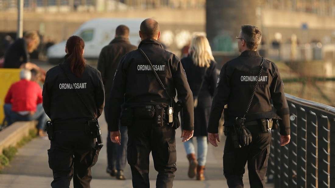 Mitarbeiter vom Ordnungsamt sind am Fußstreife am Rhein.